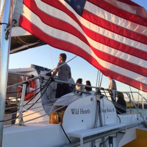 People aboard Sail Wild Hearts with American Flag